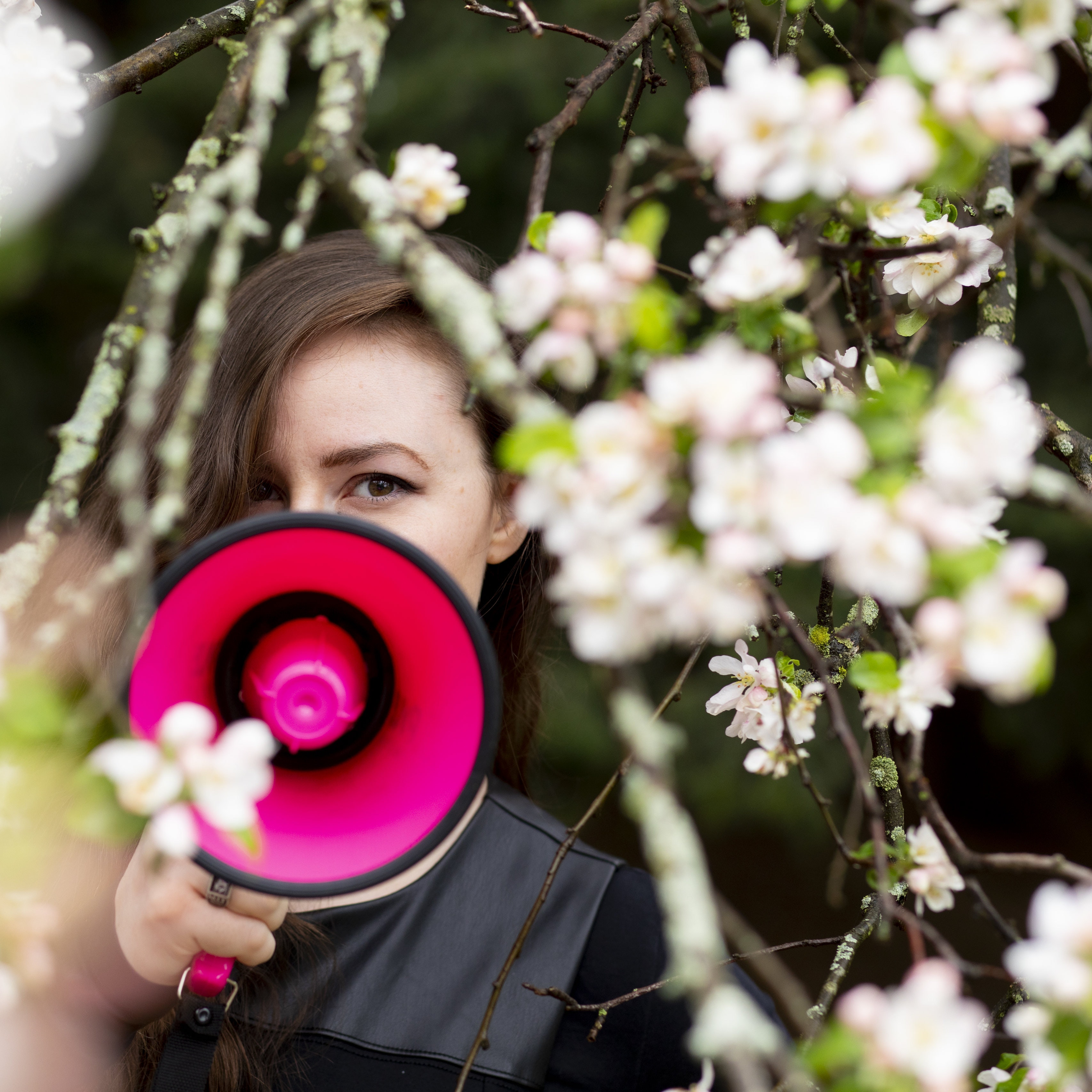 A woman stands among the lilacs, her face partially obscured by a fuchsia megaphone.