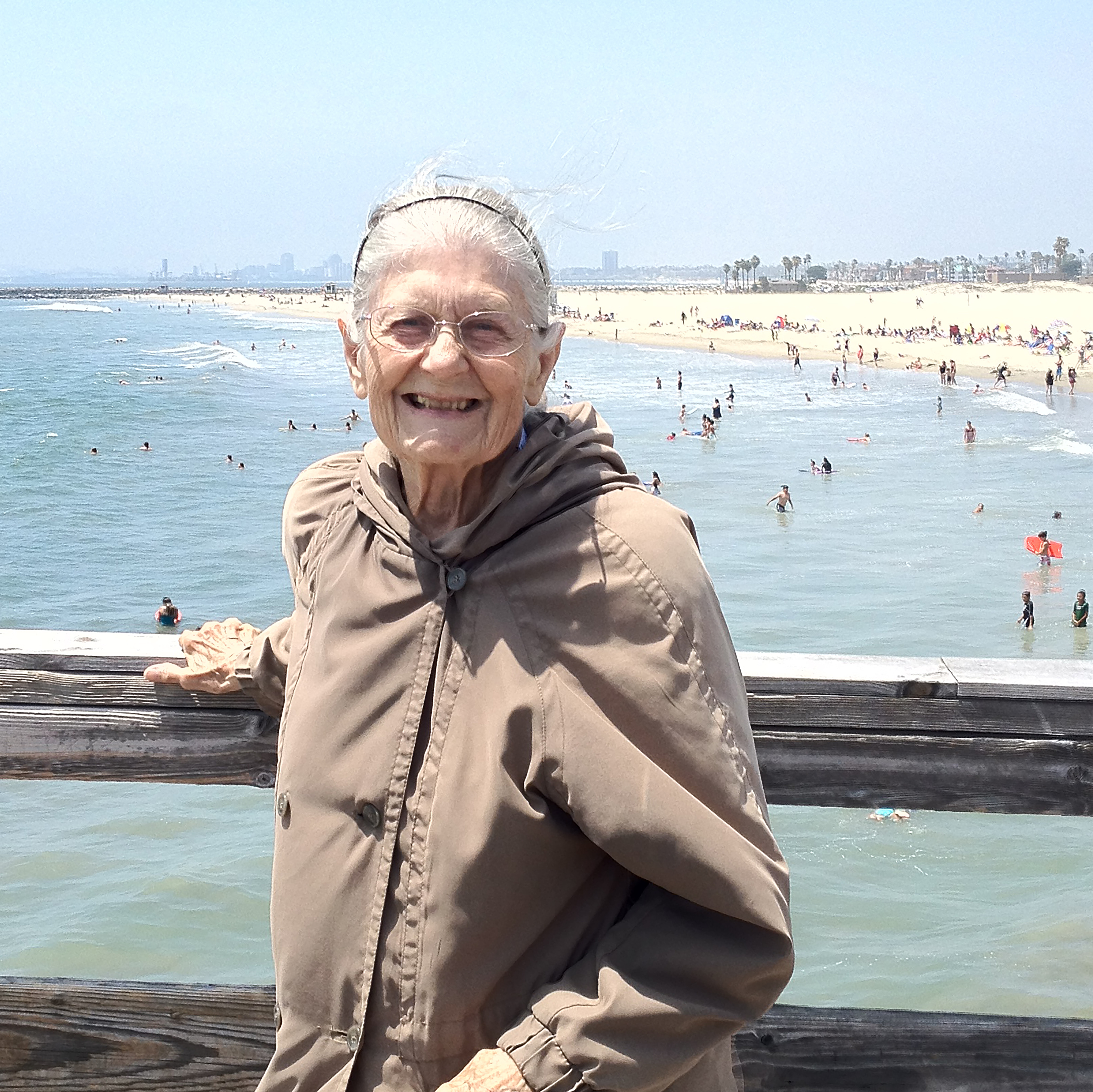 An older woman poses, smiling, at a wooden railing; in the distance behind her, people at the beach.