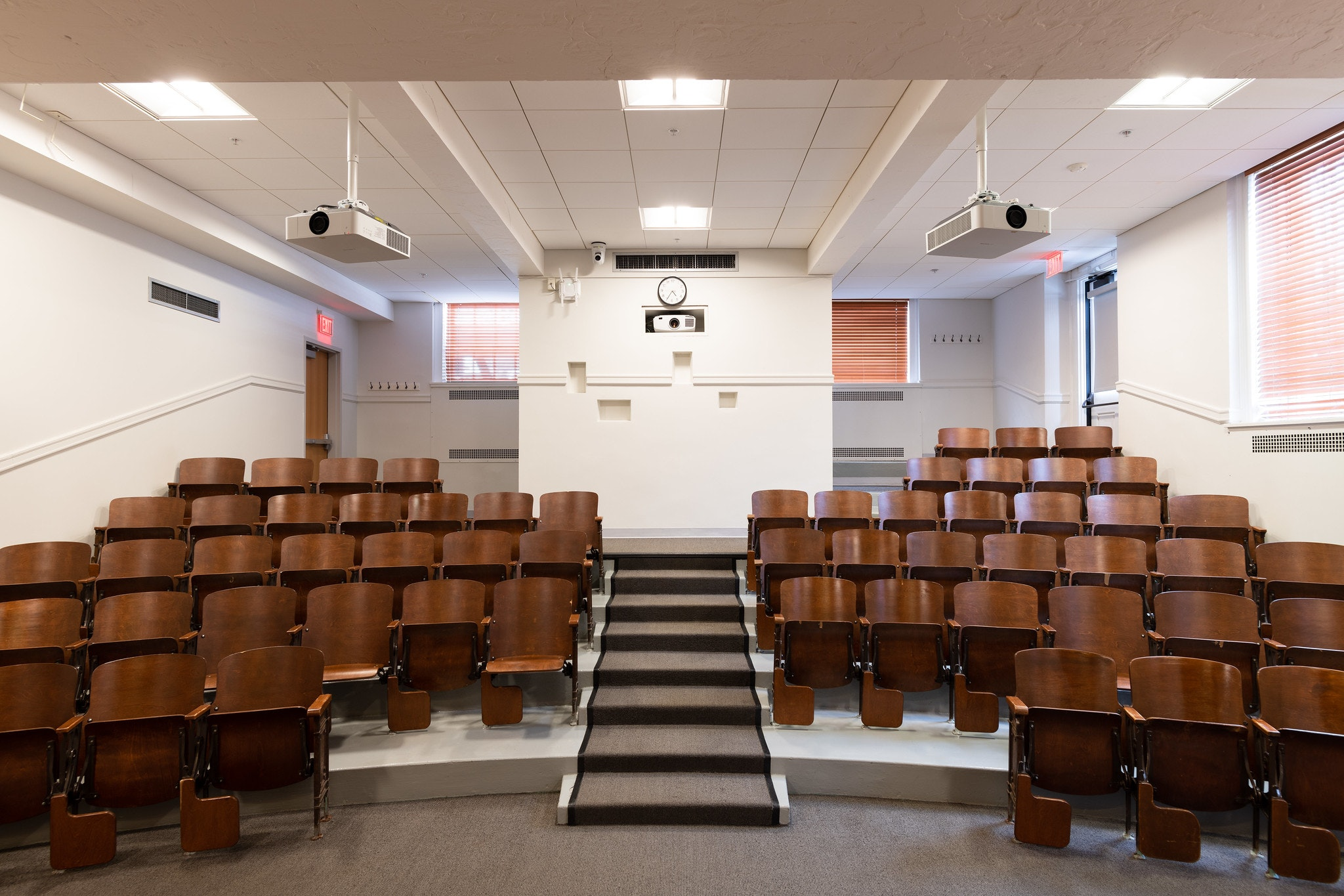 View of classroom, facing the seats. Stairs with grey carpet lining split the seating arrangement down the middle.