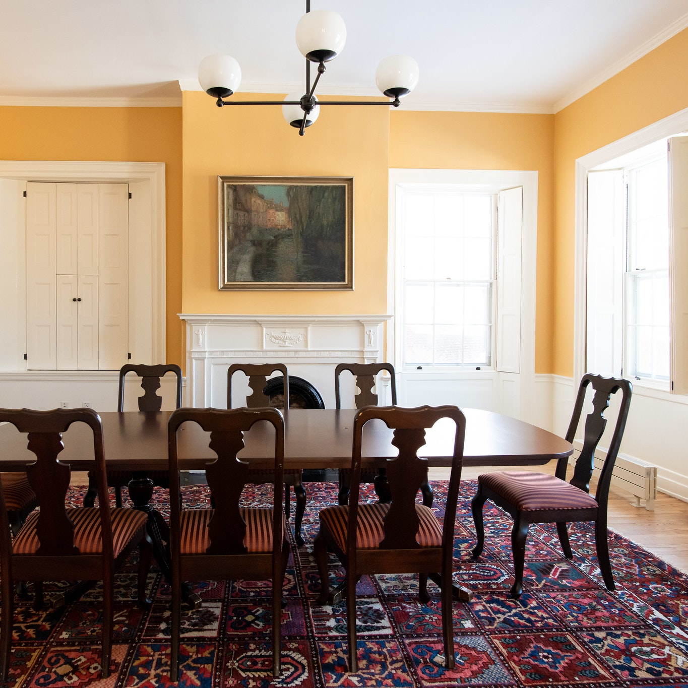 View from the entrance, dark brown wood conference table with 8 seats lined around. Fireplace and painting are on the other side of the room, behind the conference table. Walls are yellow.