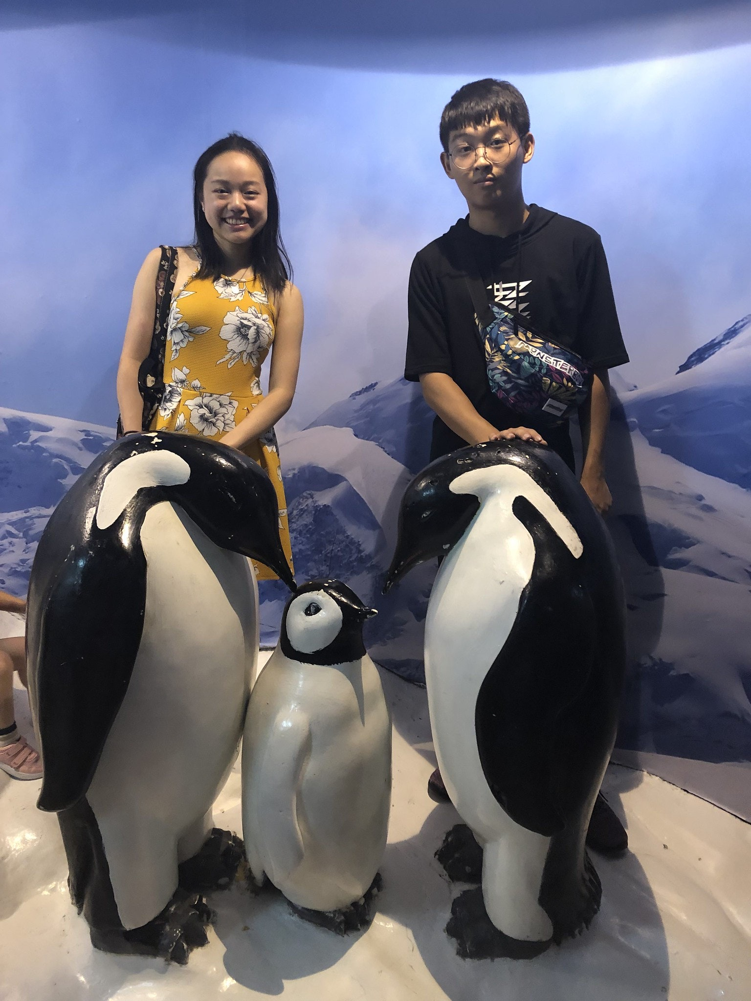 Vanessa Hu and cousin sitting on penguin sculptures at the Shanghai aquarium