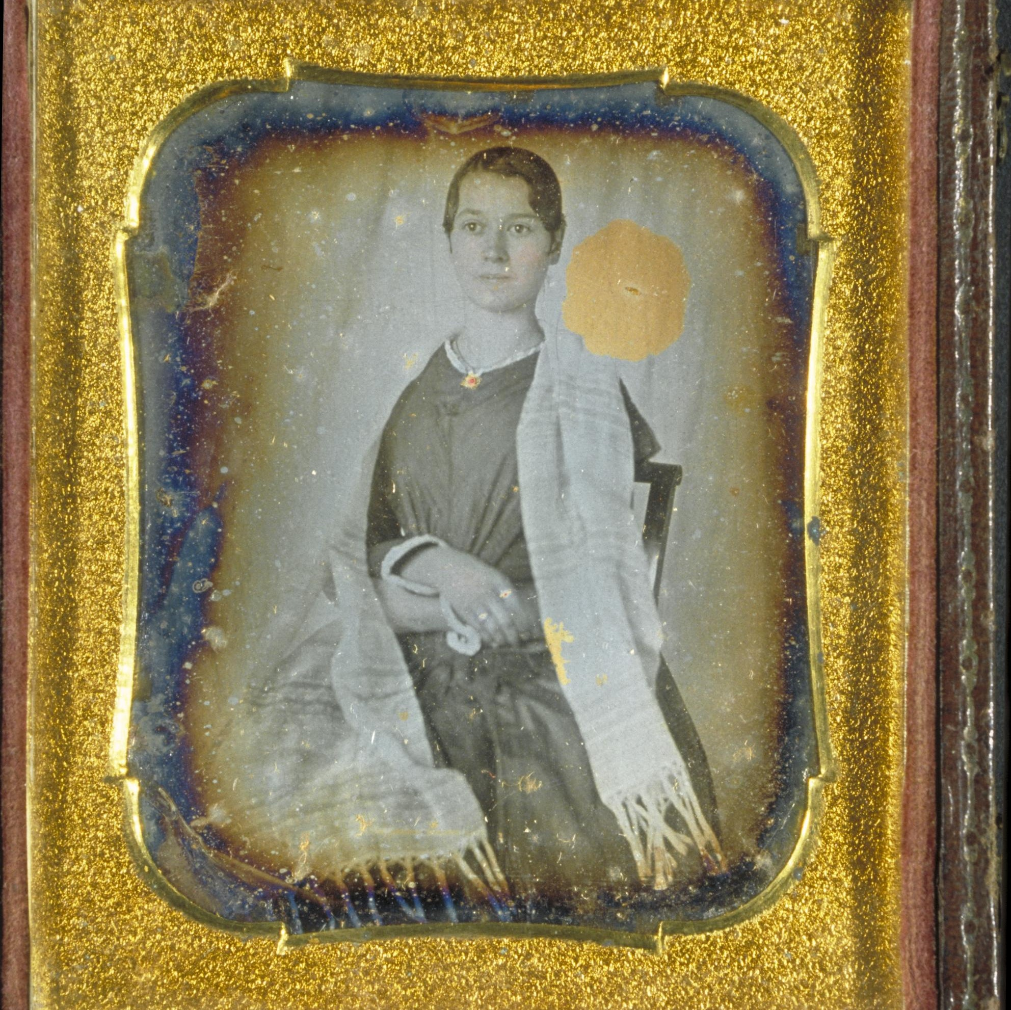 A discolored daguerreotype portrait of Elizabeth Blackwell, wearing a white shawl, set in a an elaborate gold frame.