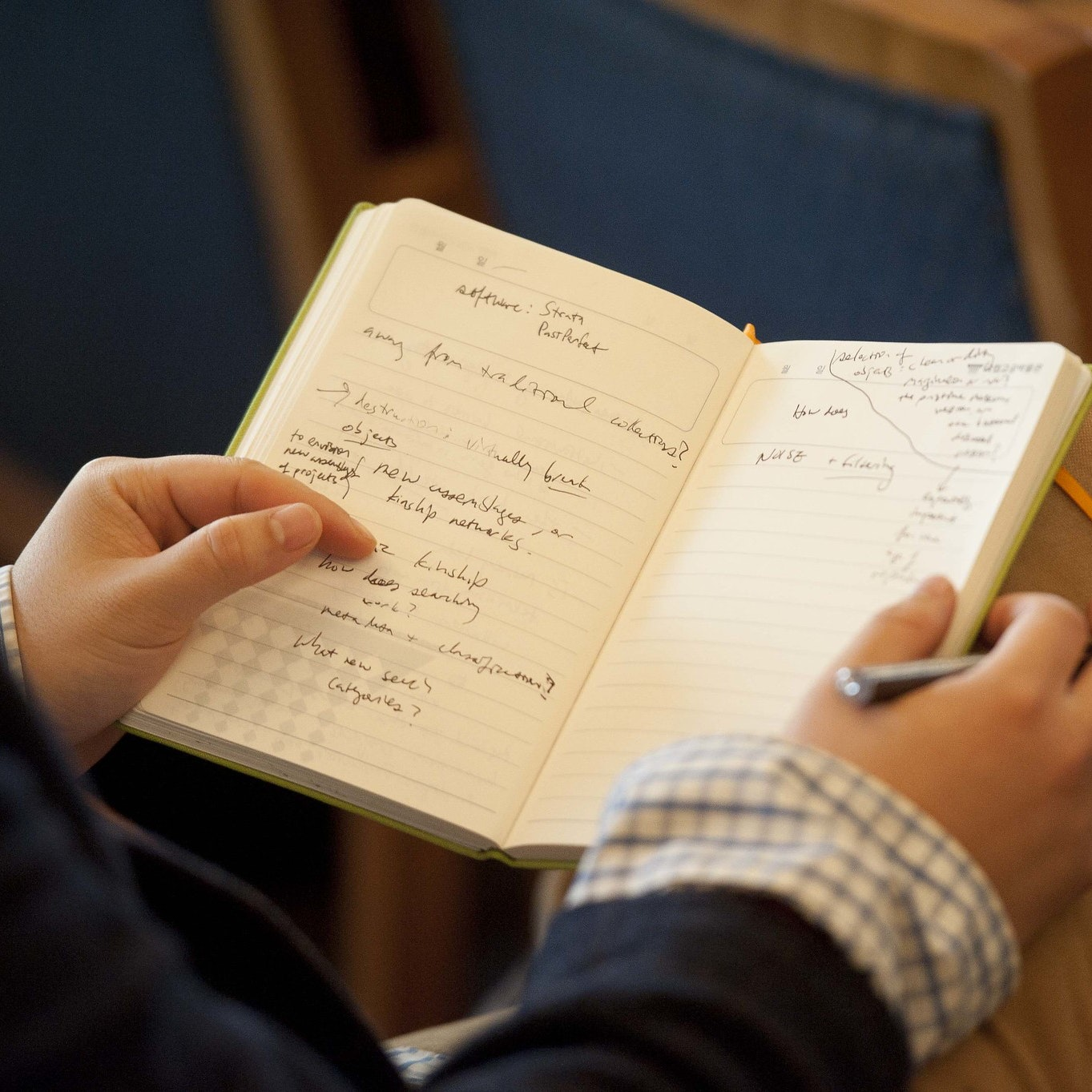 A person holds open a journal with notes on both pages.