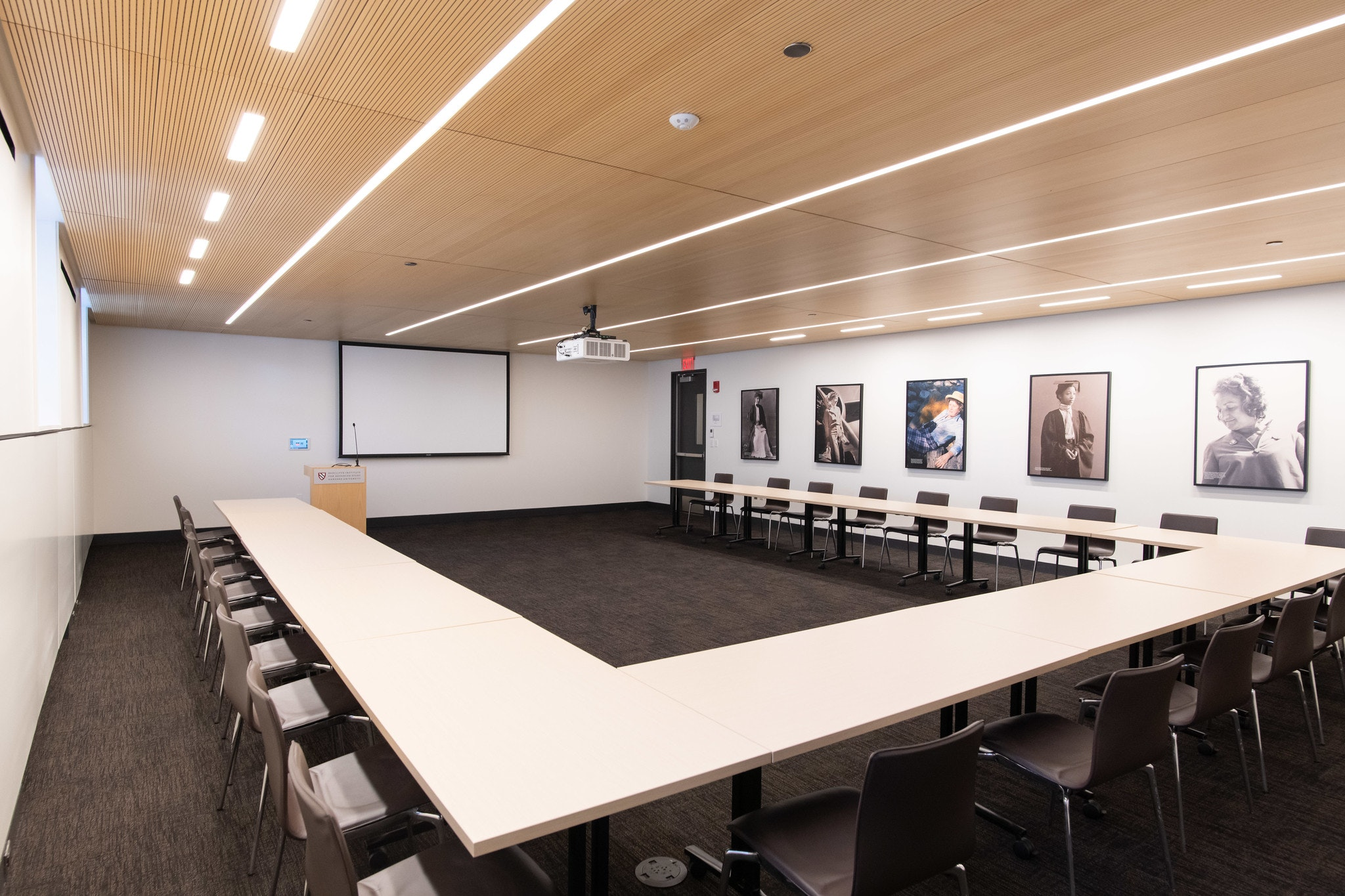 View from back of the room. Seating is set up in U-Shape for 24 people. In the front of the room is a podium and white projector screen behind it.