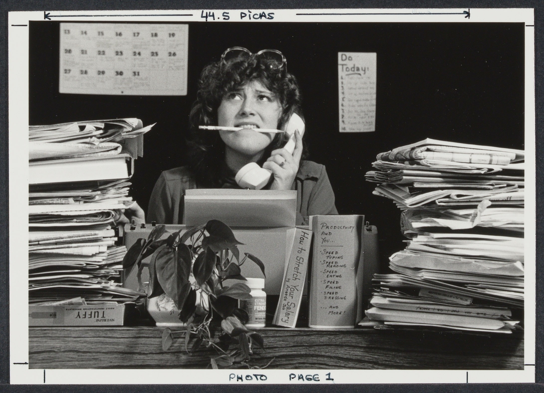 Woman posing at a desk with piles of paper stacked around her