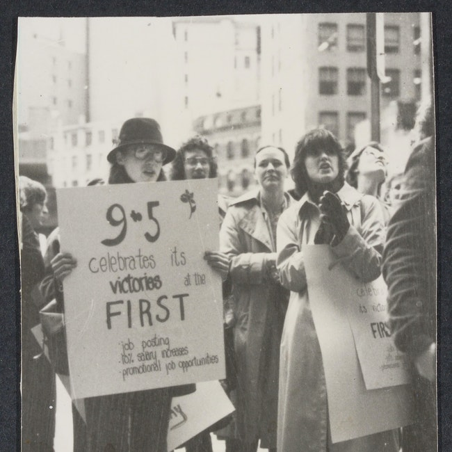Group of people holding posters at the First National Bank rally