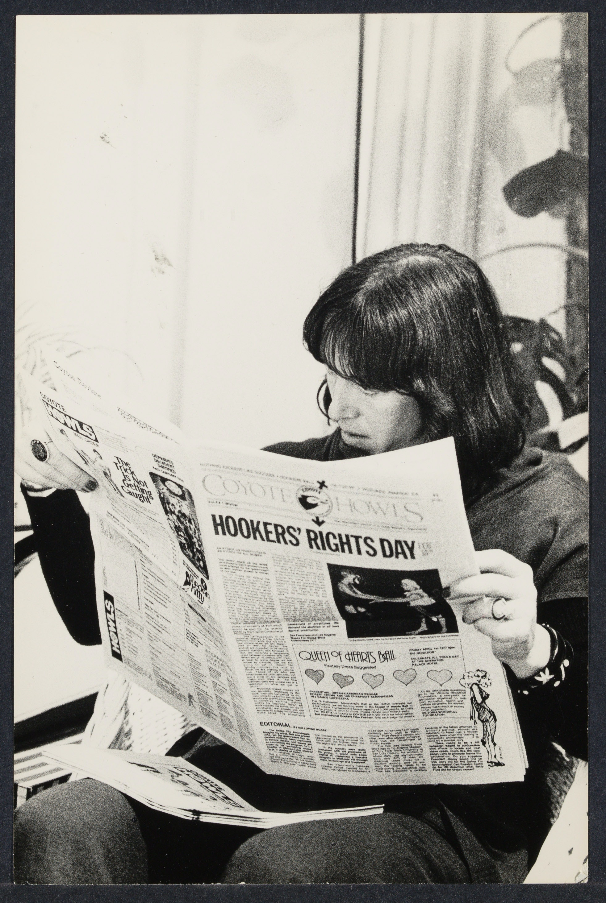 Margo St. James reading a newspaper at the Battered Women's conference