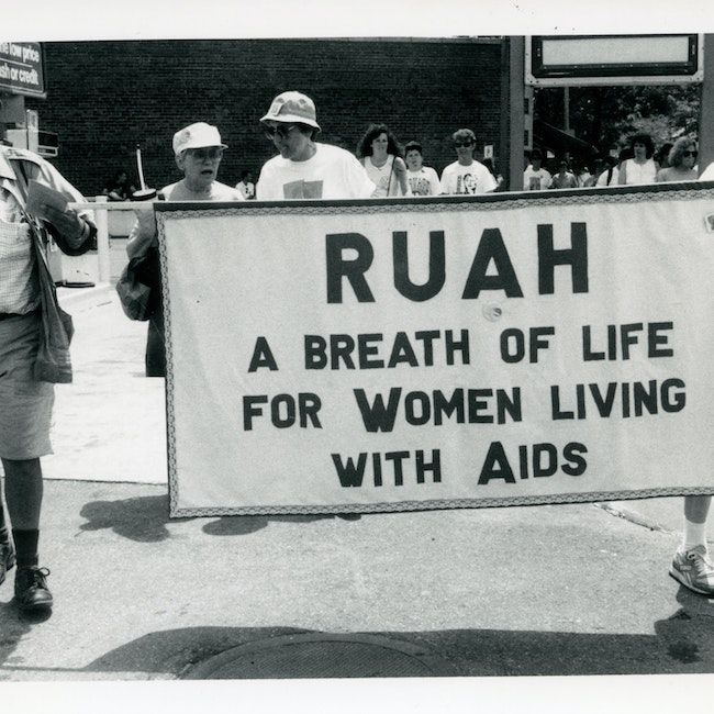 """Kip Tiernan and Sr. Jeanette marching with Ruah (interfaith organization) banner. Text reads """"A breath of life for women living with AIDS"""", 1991"""
