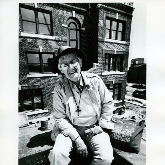 Kip Tierman smiling, and seated outdoors on a rooftop, ca. 1991.