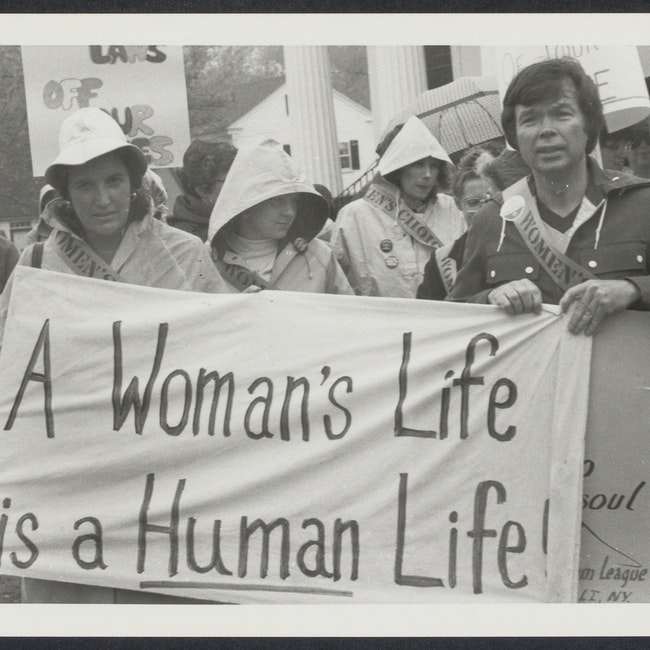 "Norma Swenson (left) and Bill Baird (right) holding banner that states ""A Woman's Life is a Human Life"" at event"