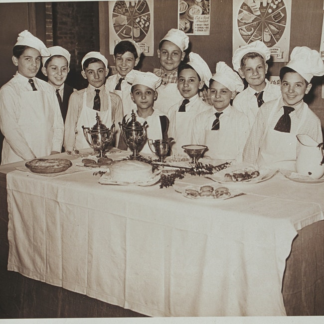 Portrait of ten boys in cooking class, standing in front of nutrition poster display and behind table of food