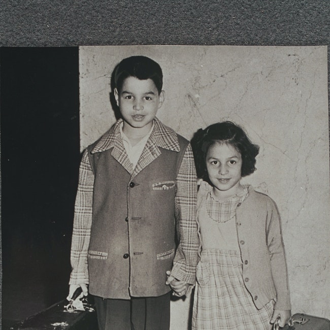 Brother and sister holding hands, carrying suitcases