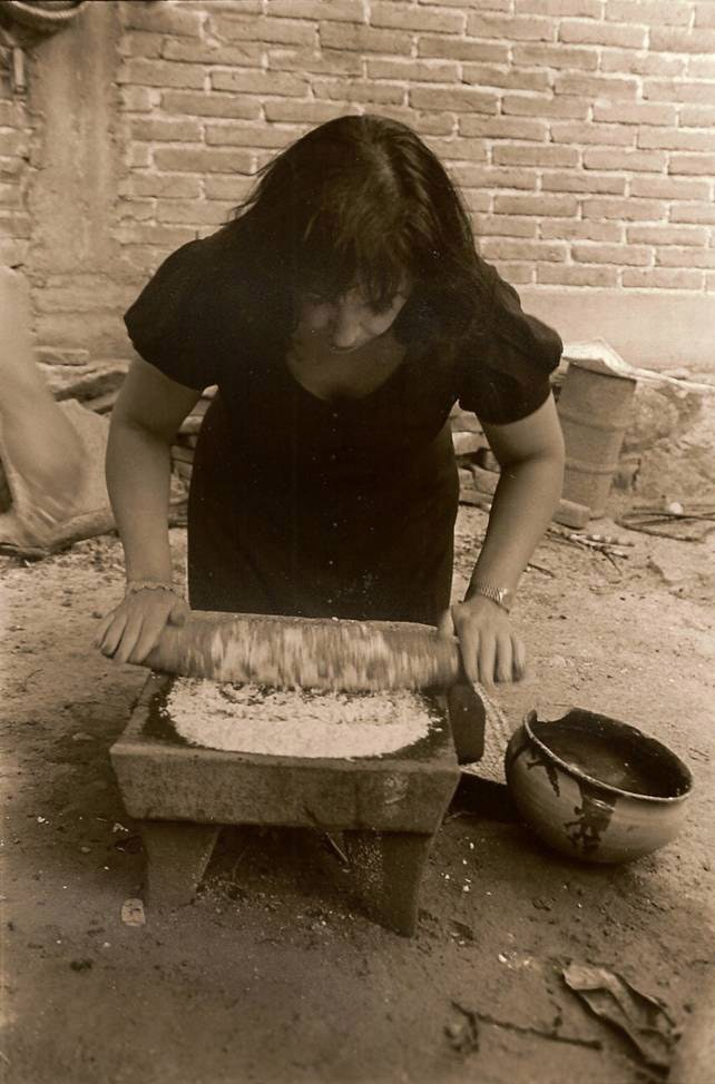 Zarela Martinez grinds cornmeal with a traditional metate in Oaxaca