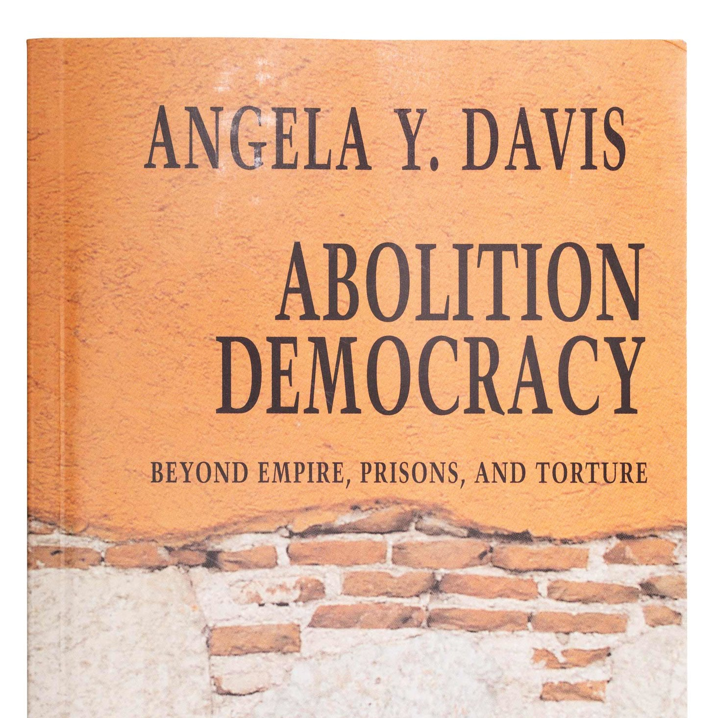 """Angela Davis Bookcover, """"Abolition Democracy."""" Bookcover illustration consists of a brick wall."""