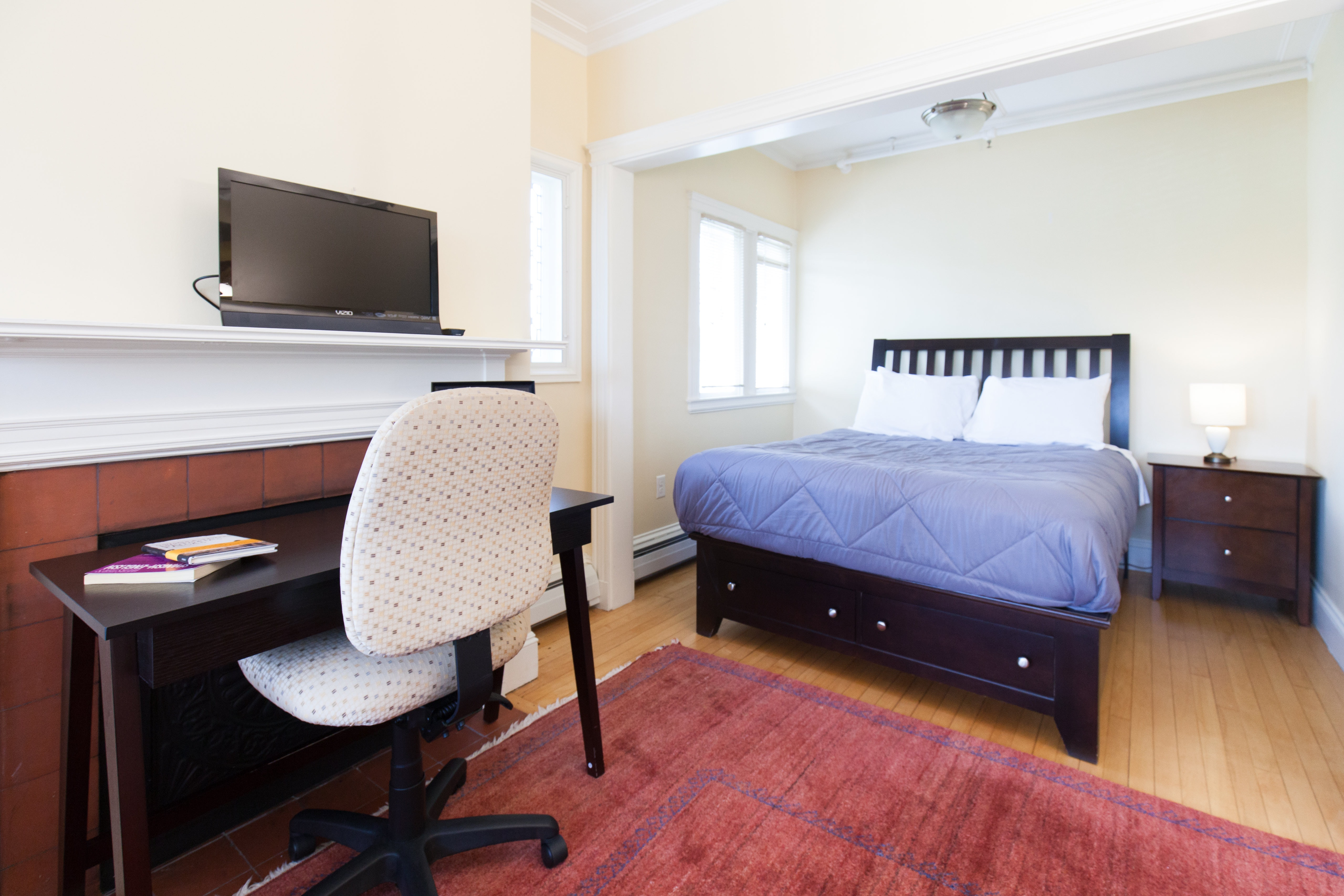 Living area of 83 Brattle Street studio apartment with alcove with bed, night table, desk, and chair