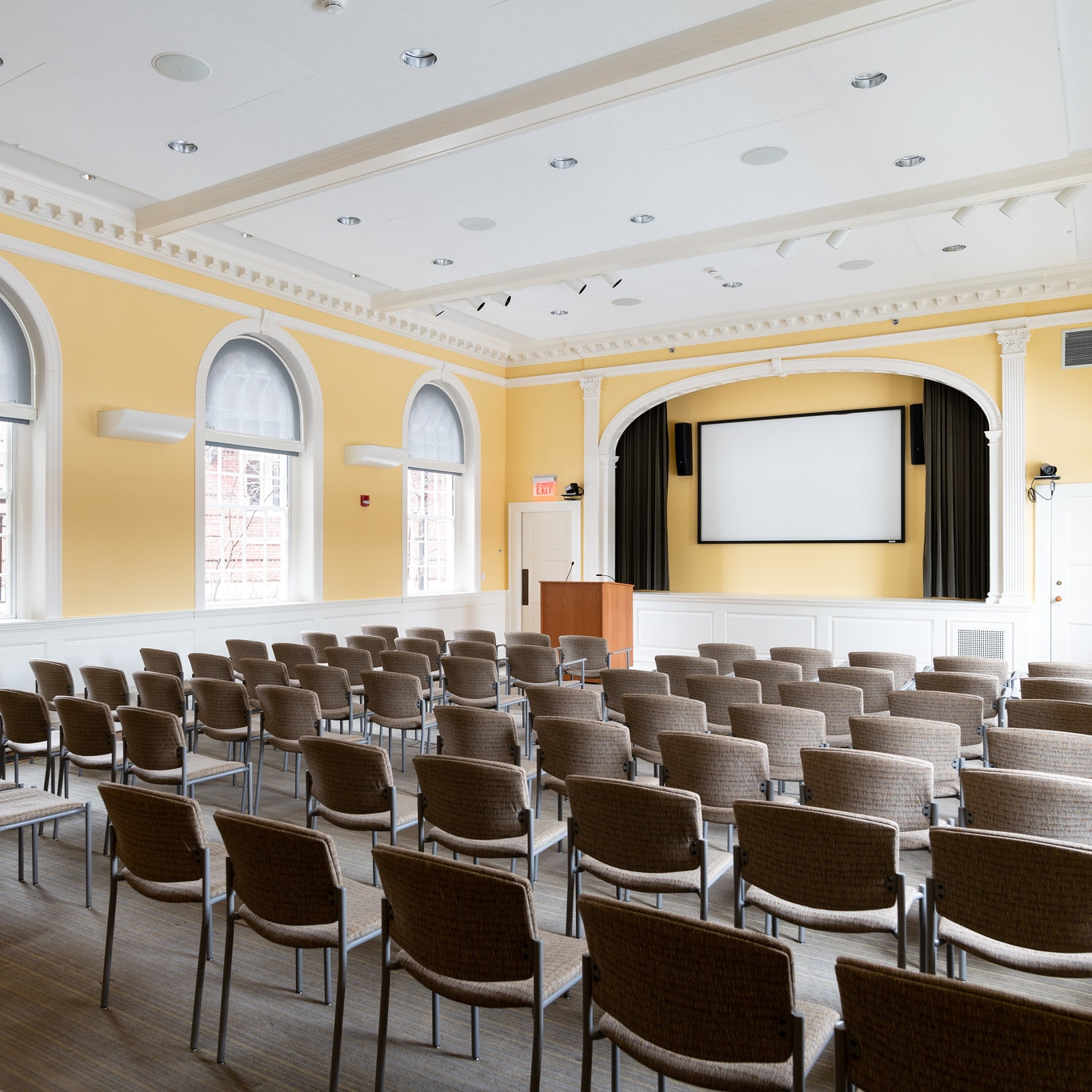 Theatre style setup for seating, with white projector in the front middle of the room, mounted to wall. Windows lining the east and west sides of the room. Walls are yellow.