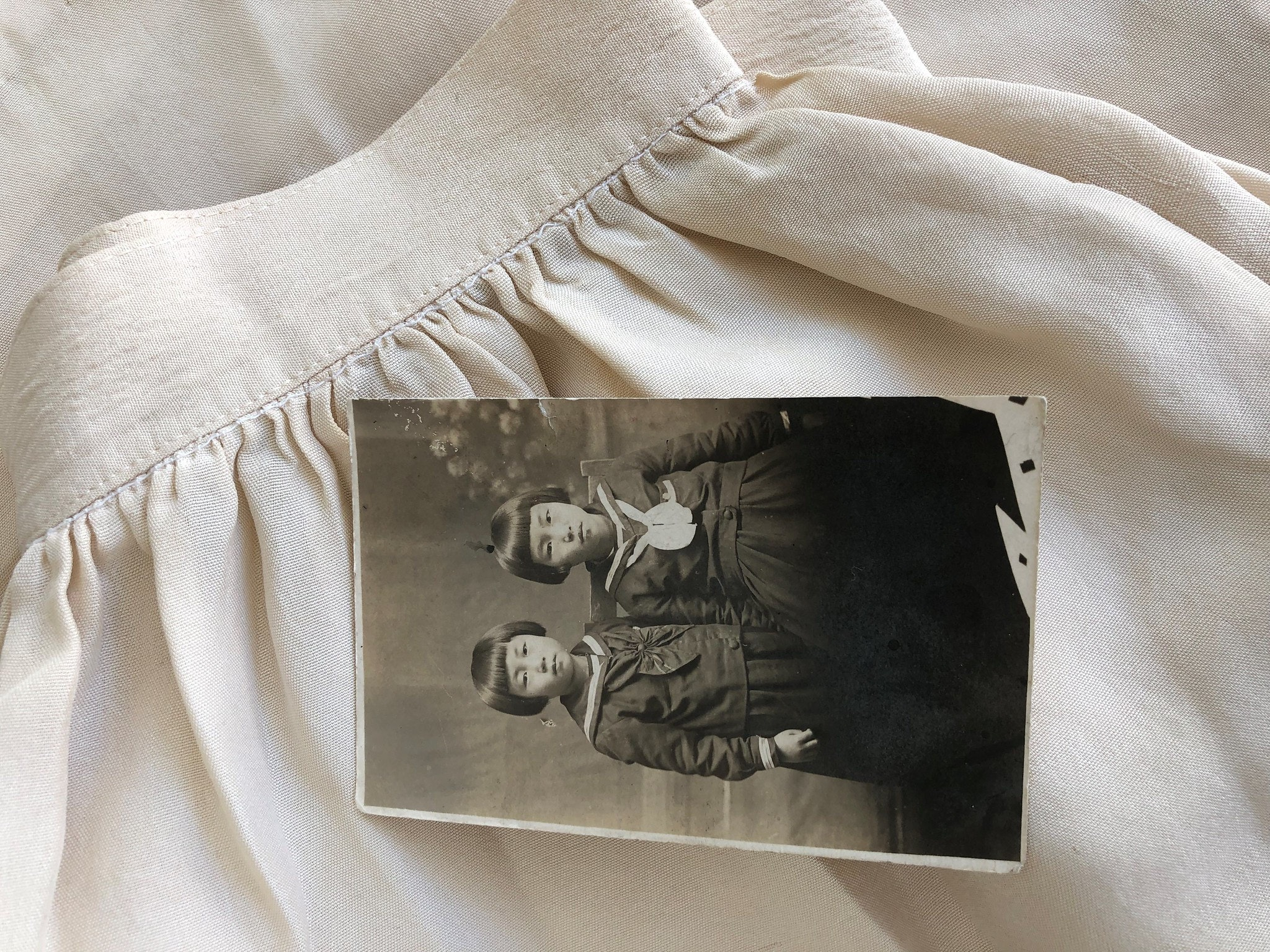 Sepia toned photo of Jeannie Park's mother and aunt. Photo rests on a skirt from handmade silk