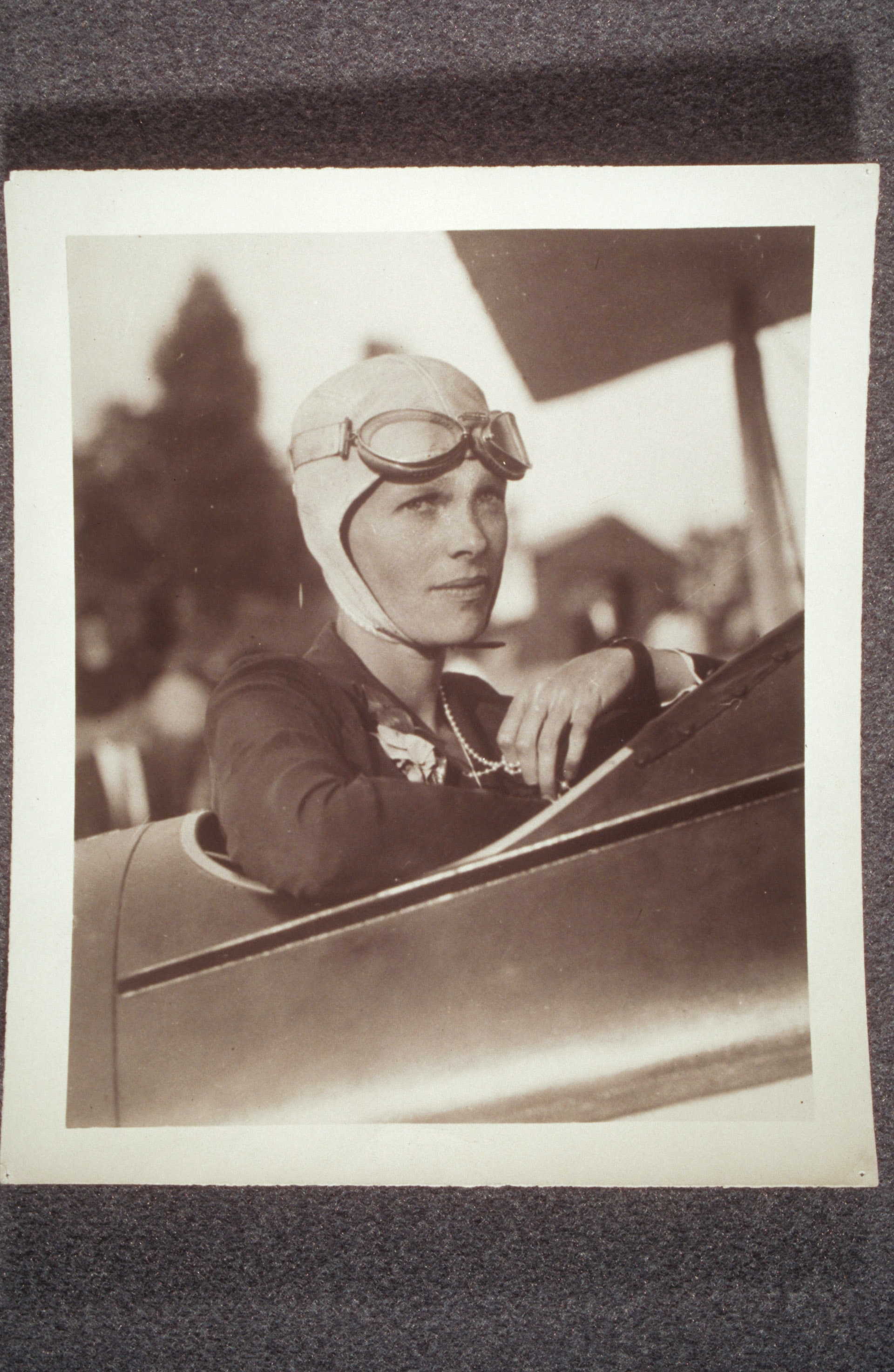 Amelia Earhart, in plane, wearing flight helmet and pearls