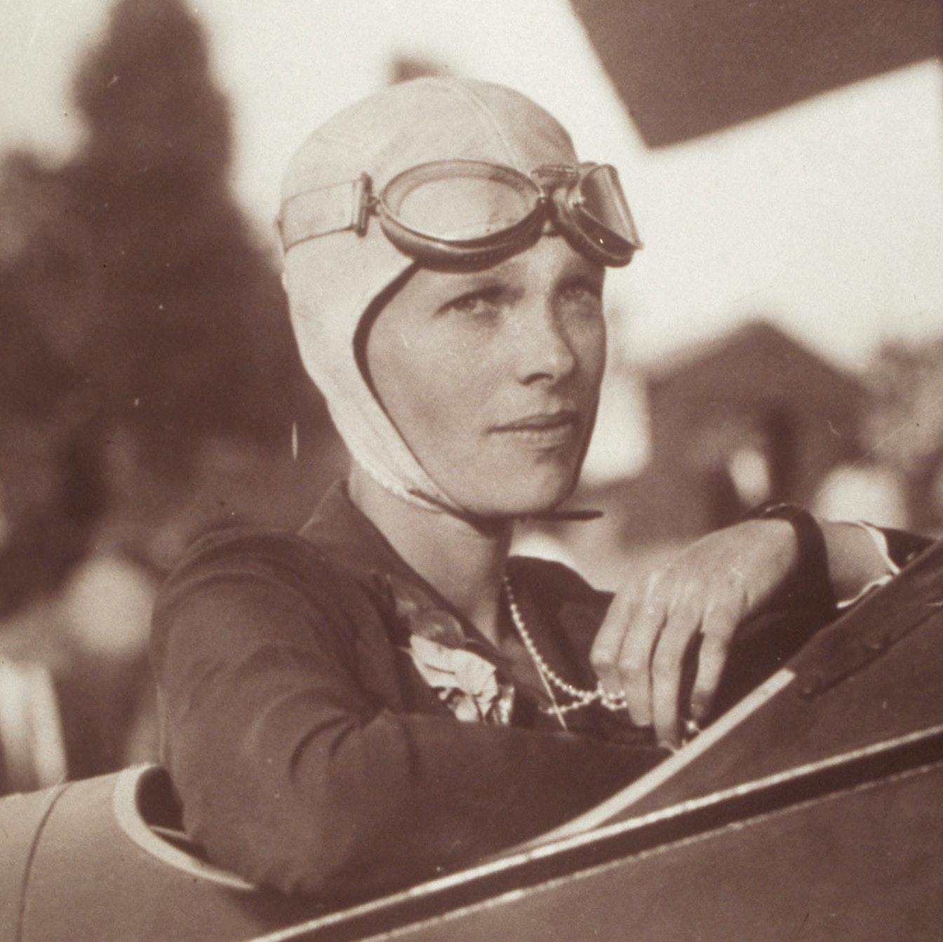 Amelia Earhart, in plane, wearing flight helmet and pearls