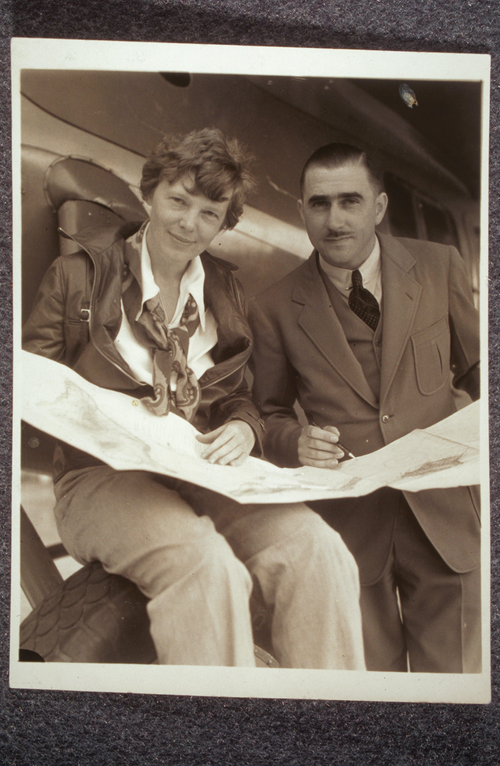 Amelia Earhart and Paul Mantz looking at a flight chart or map together