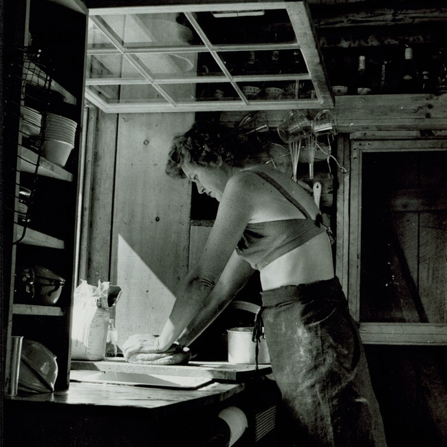 Julia Child kneading dough by an open kitchen window