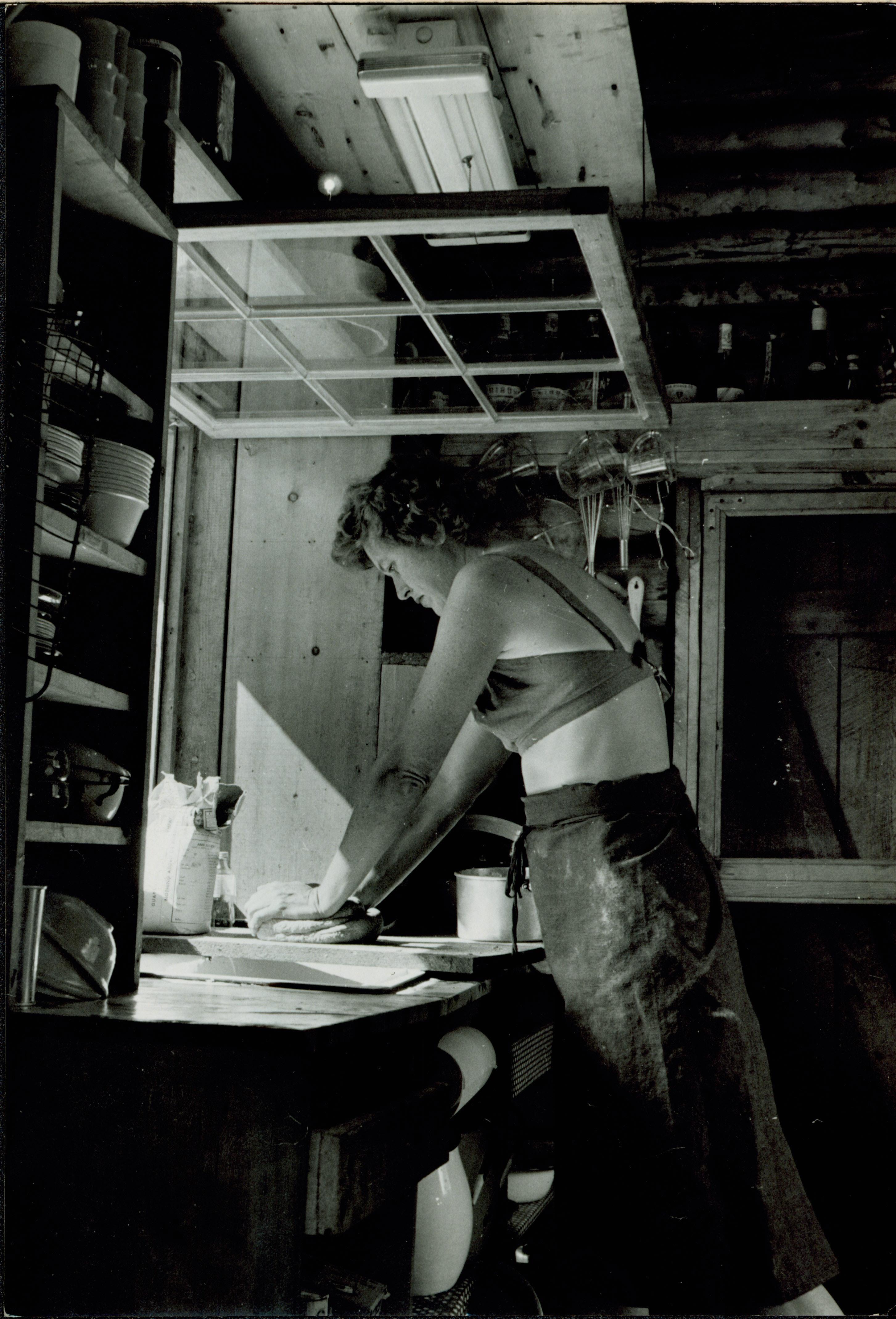 Julia Child kneading dough by an open kitchen window