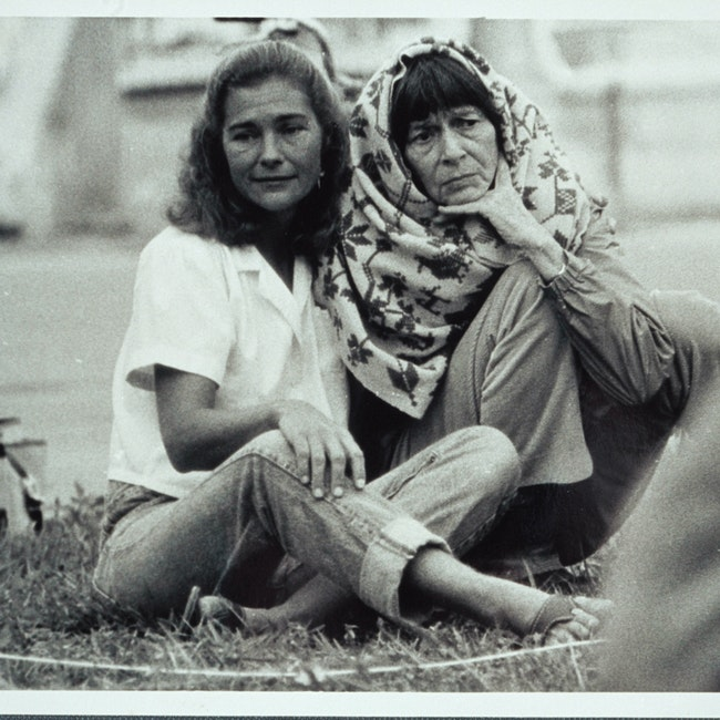 Barbara Deming, wrapped in a shawl, and an unidentified woman seated on the ground