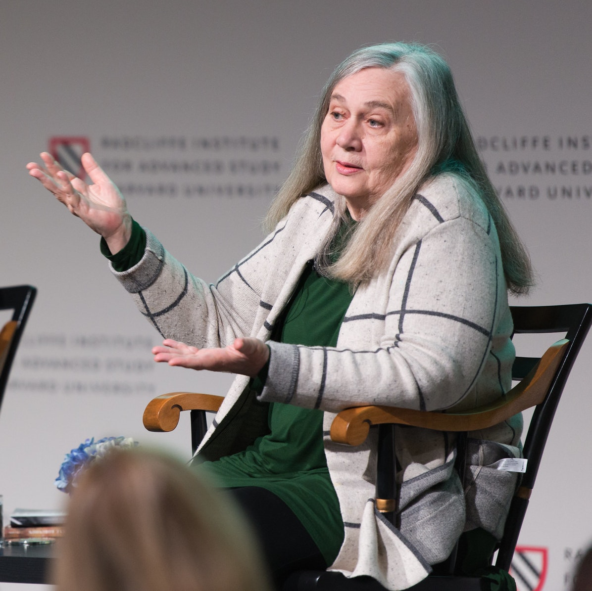 An image of Marilynne Robinson and James Wood sitting in chairs on a stage.