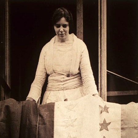 Alice Paul draping the Ratification Banner at the headquarters of the National Womens Party_August 20 1920_courtesy of Schlesinger Library
