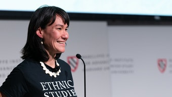 """A woman stands at a podium speaking, wearing a t-shirt that says """"Ethnic Studies Now."""""""