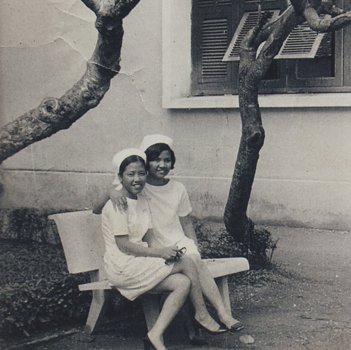 Sepia toned image of Hồng-Ân Trương's mother and her classmate sitting on a bench at 17 years old.