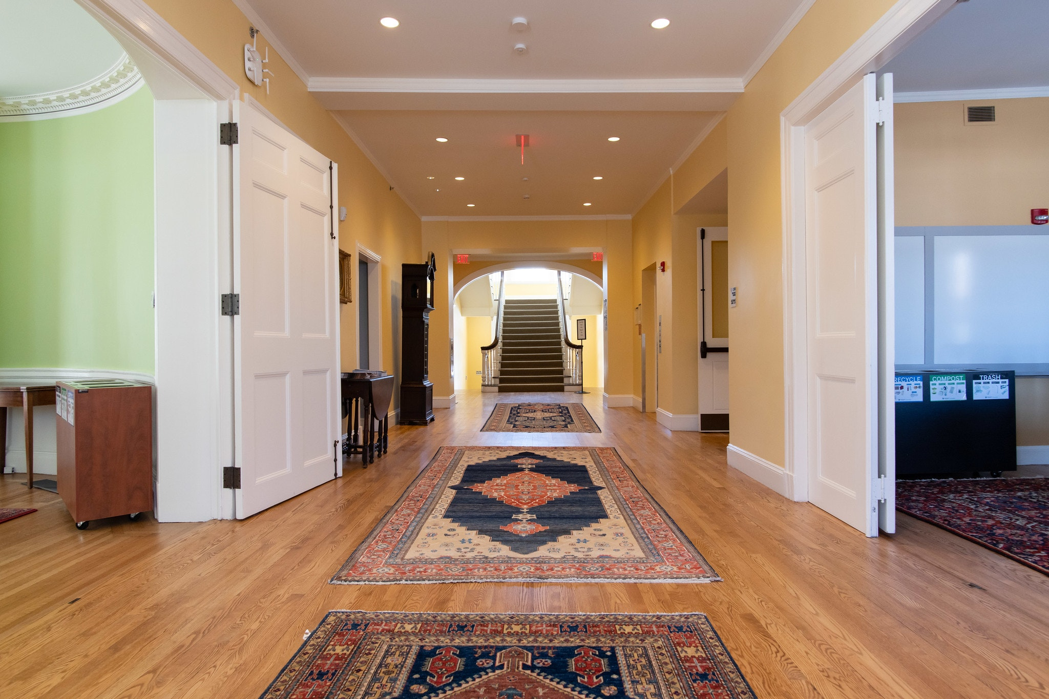 Lobby with wood floors and three printed rugs. At the end of the lobby there is a dark brown staircase leading upstairs.