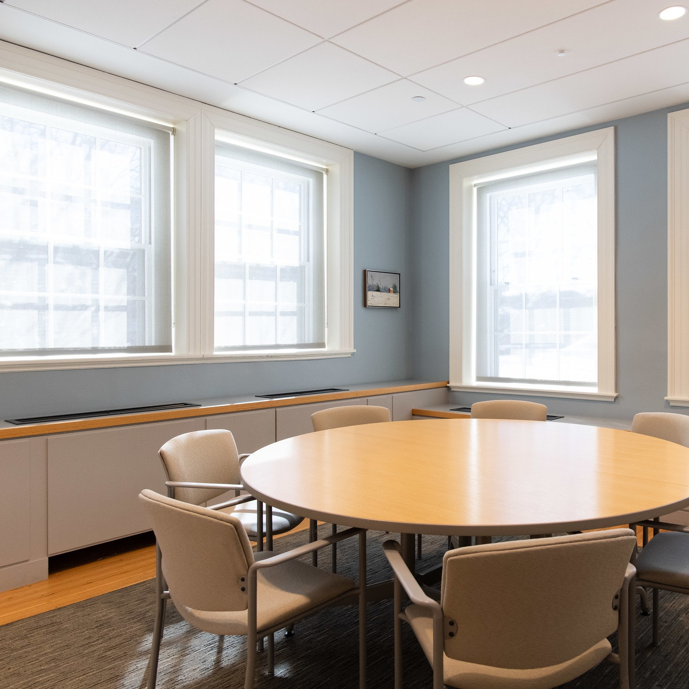 View from entrance of circular conference room table, seating for 7 people. Natural light from windows entering the room.