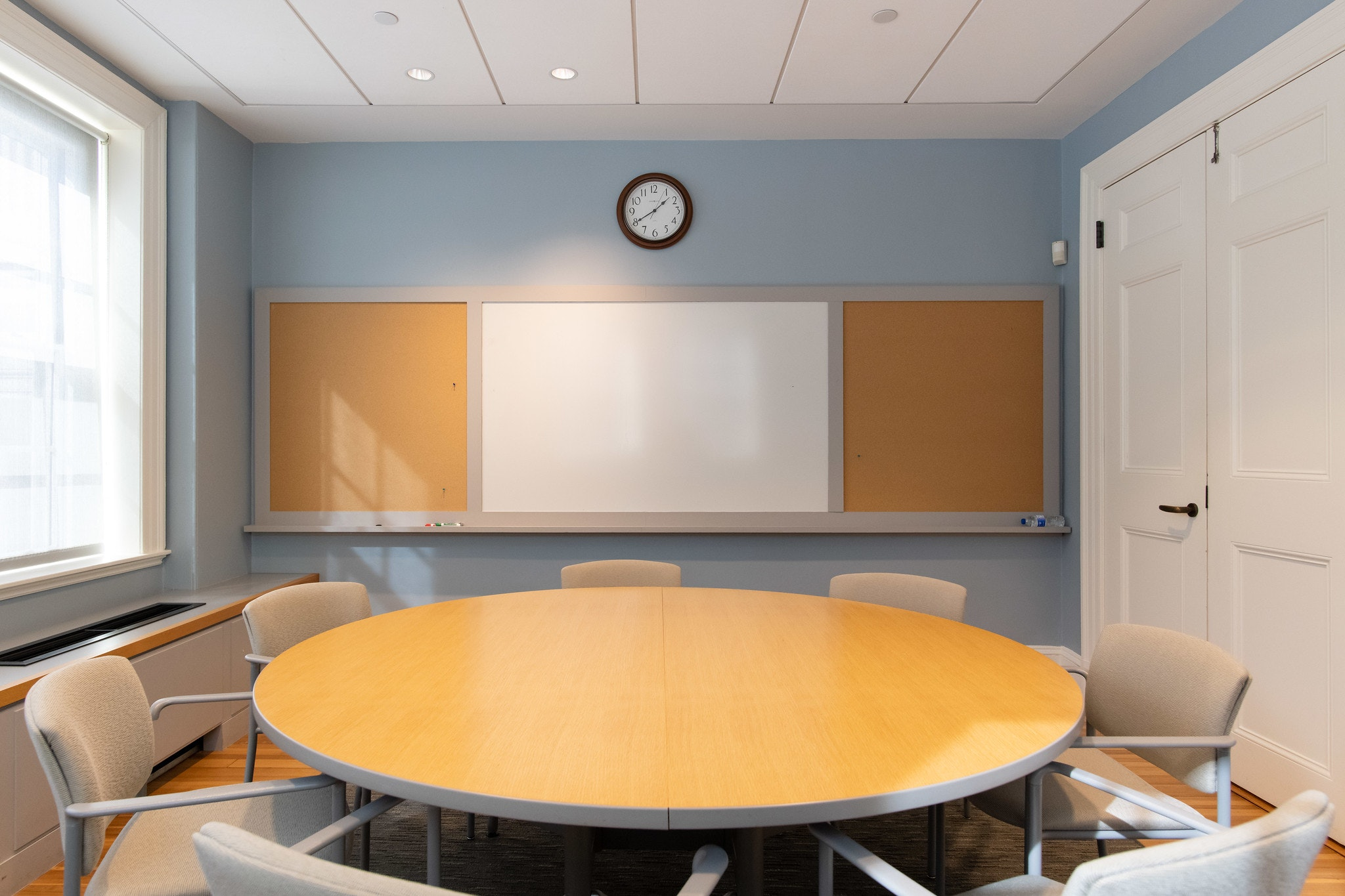 Circular conference room table, seating for 7 people. To the right is an entrance of two white double doors, and to the left are some windows letting in natural light. In the back center of the room is a whiteboard and a clock mounted directly above it.