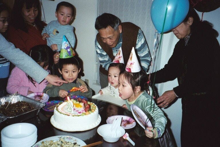 Vanessa Hu sitting around table for her 5th birthday party. Sister assists with blowing out candle.
