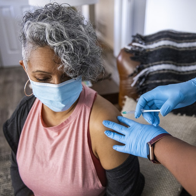 Nurse giving a Covid-19 vaccine to a senior Black woman.