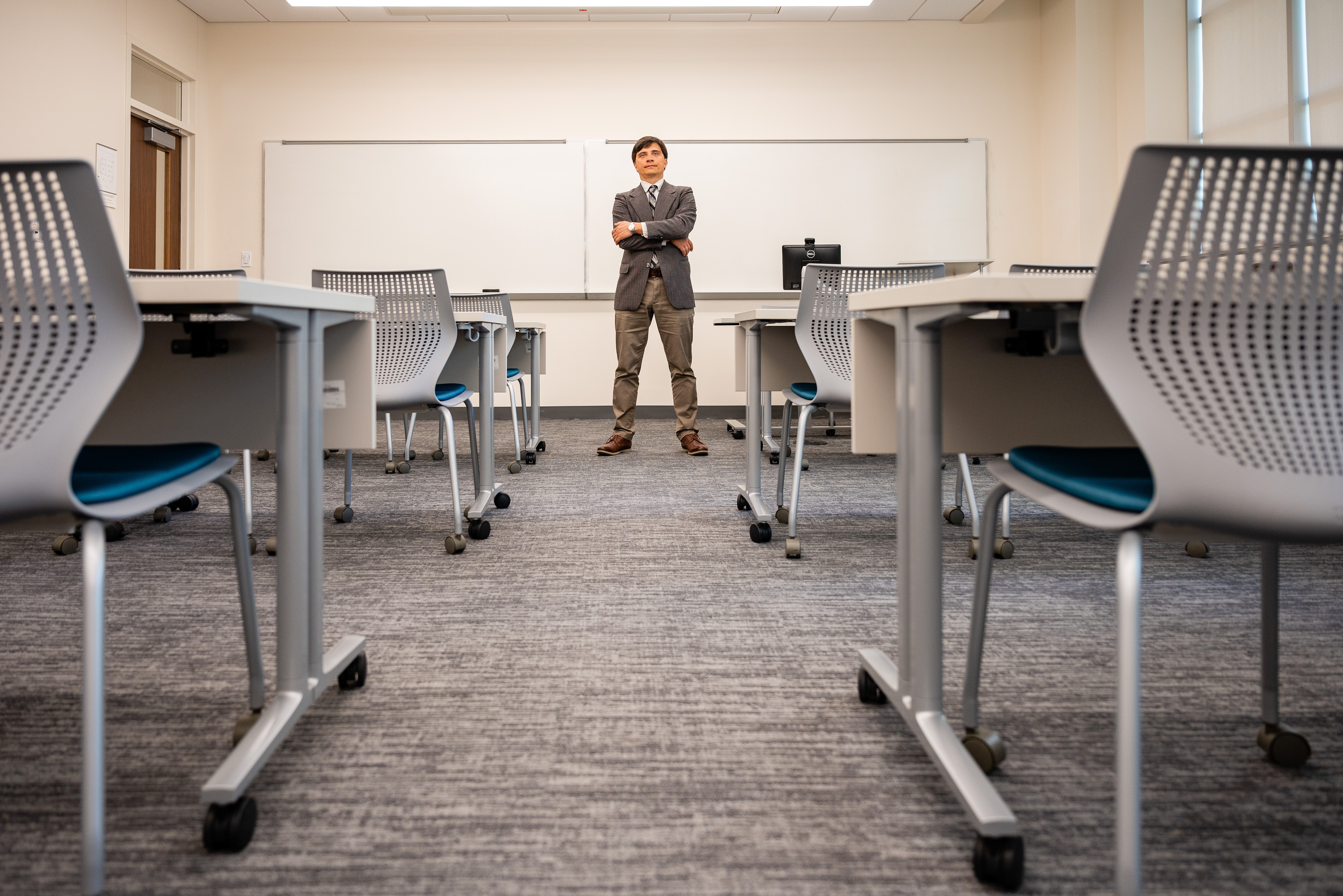 A man stands, arms crossed, in front of a classroom whiteboard. In the foreground, empty chairs.