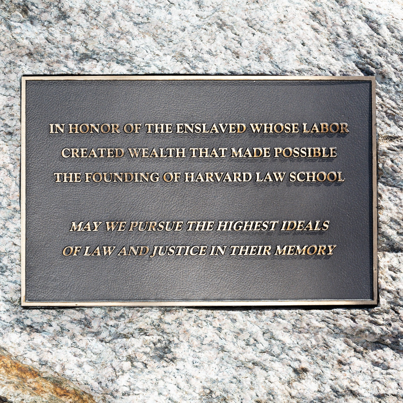 """Plaque reading: """"In honor of the enslaved whose labor created wealth that made possible the founding of Harvard Law School. May we pursue the highest ideals of law and justice in their memory."""""""