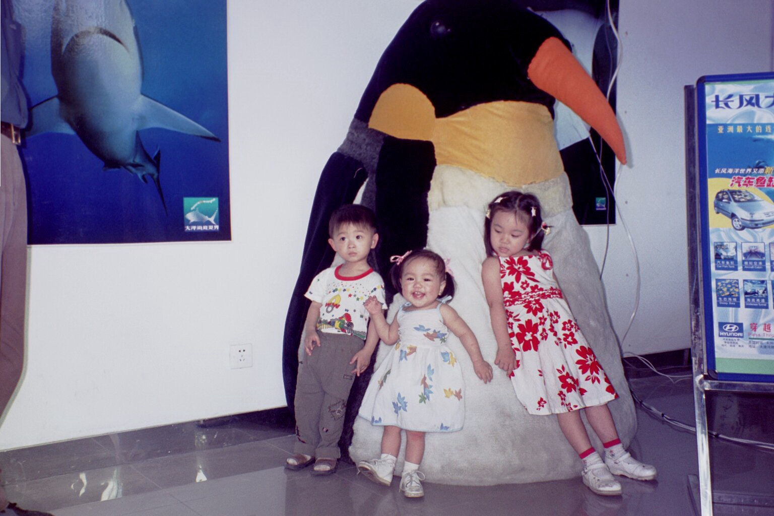Childhood Vanessa Hu with two other family members leaning on large stuffed animal penguin
