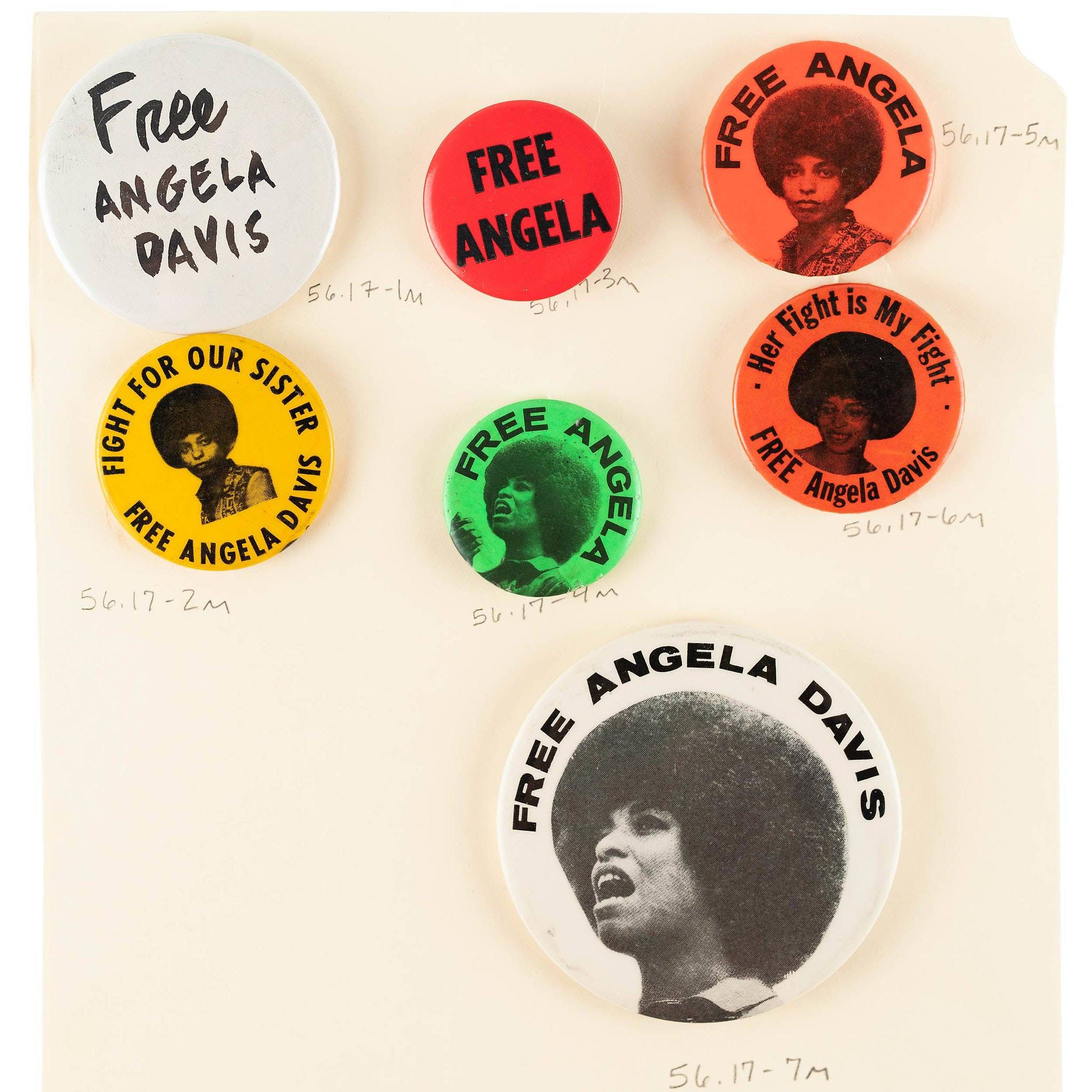"""""""Free Angela"""" buttons in red, orange, yellow, green and white. Image on buttons include Angela Davis' headshot."""
