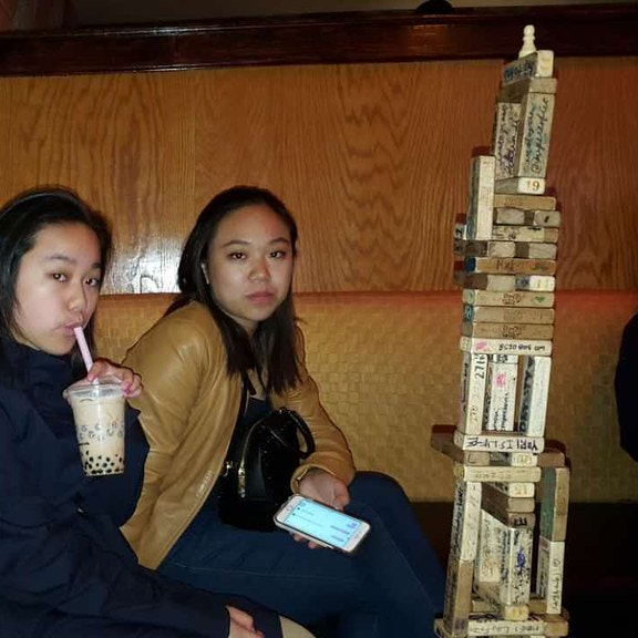 Vanessa Hu and friend sipping bubble tea and playing Jenga