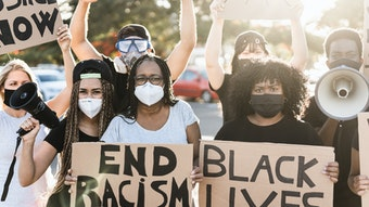 """Group of adults holding signs that read """"Black Lives Matter,"""" """"End Racism,"""" and """"Justice Now"""""""