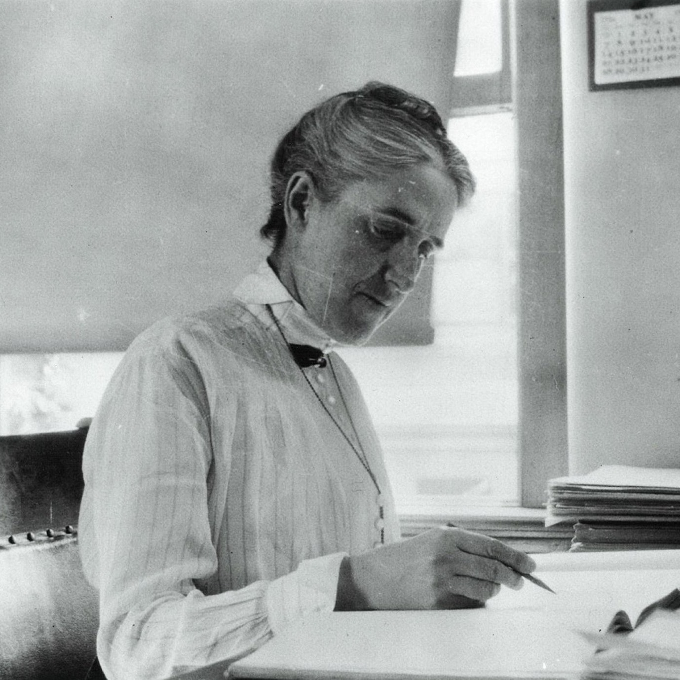 Woman sitting at a desk, pencil in hand with a book open faced.