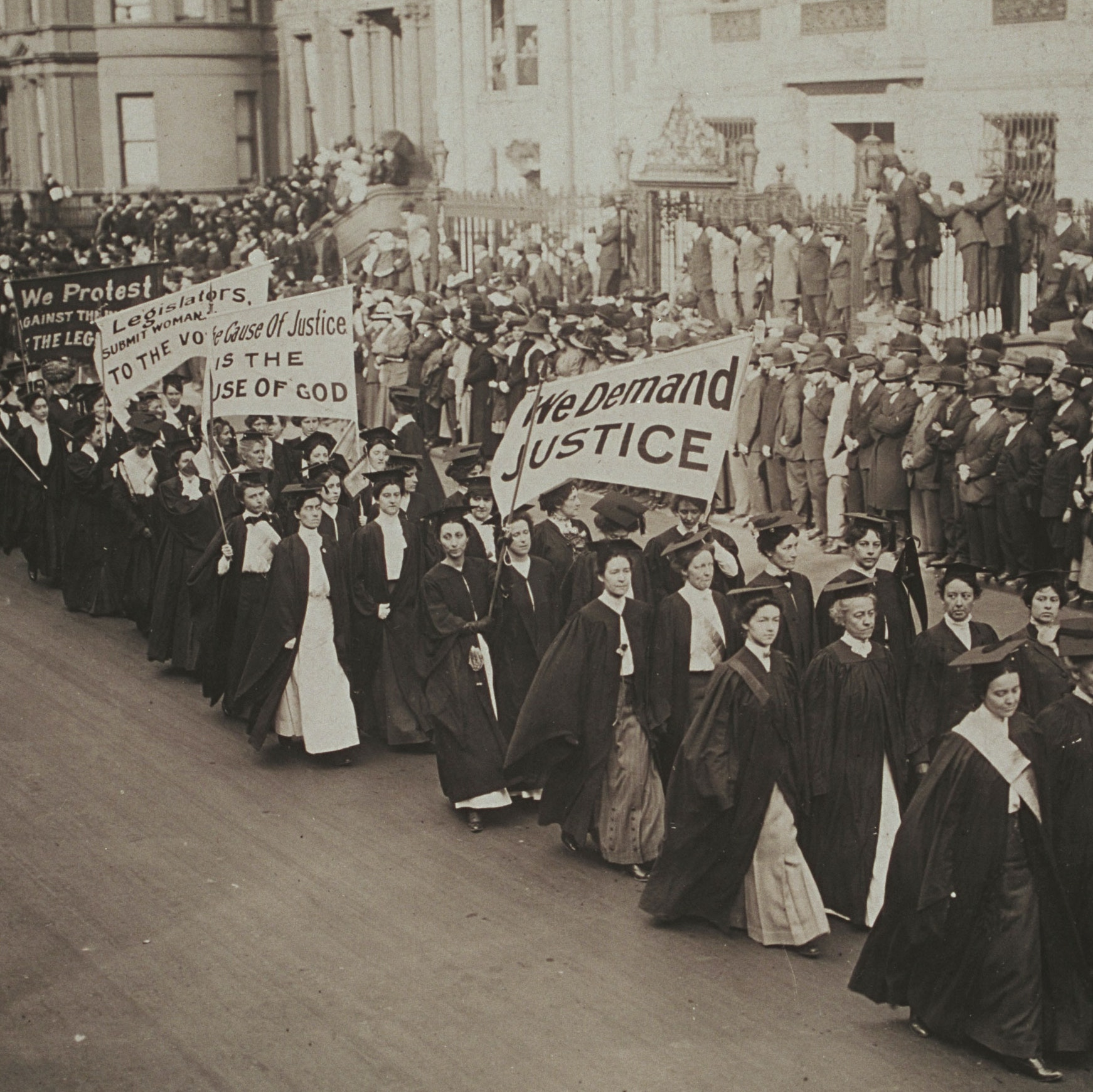 """Women in academic dress march in a suffrage parade in New York City. They carry banners that read """"We Demand Justice,"""" """"The Cause of Justice is the Cause of God,"""" """"Legislators, Submit Woman [cut off] To The Vote."""""""