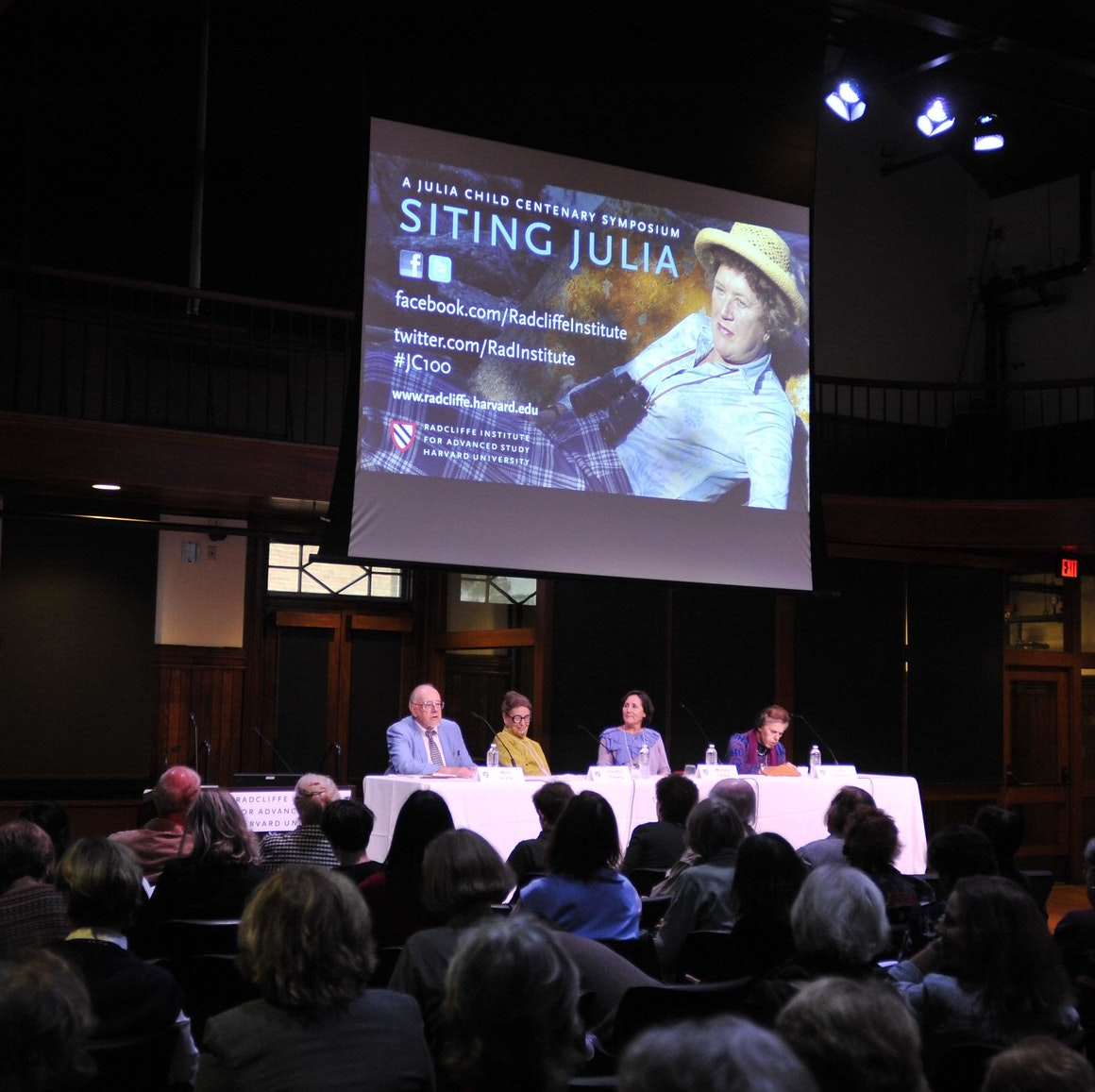"Mark DeVoto (left), Dorothy Zinberg, Michela Larson, and Jane Thompson sit at a panel table in front of an audience. A screen above them displays a photo of Julia Child and reads, ""Siting Julia."""