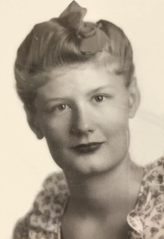 Black and white photo of a woman with a slight smile looking directly at the camera. Her hair is gathered atop her head.