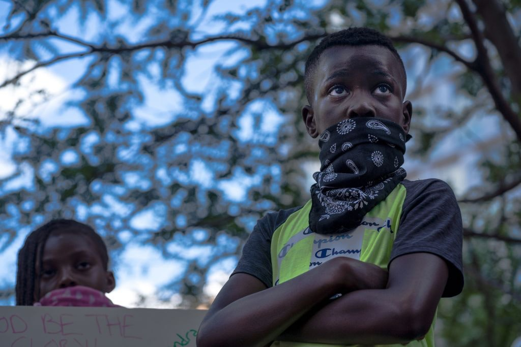 Photo of a young demonstrator at a protest in response to police killing of George Floyd.