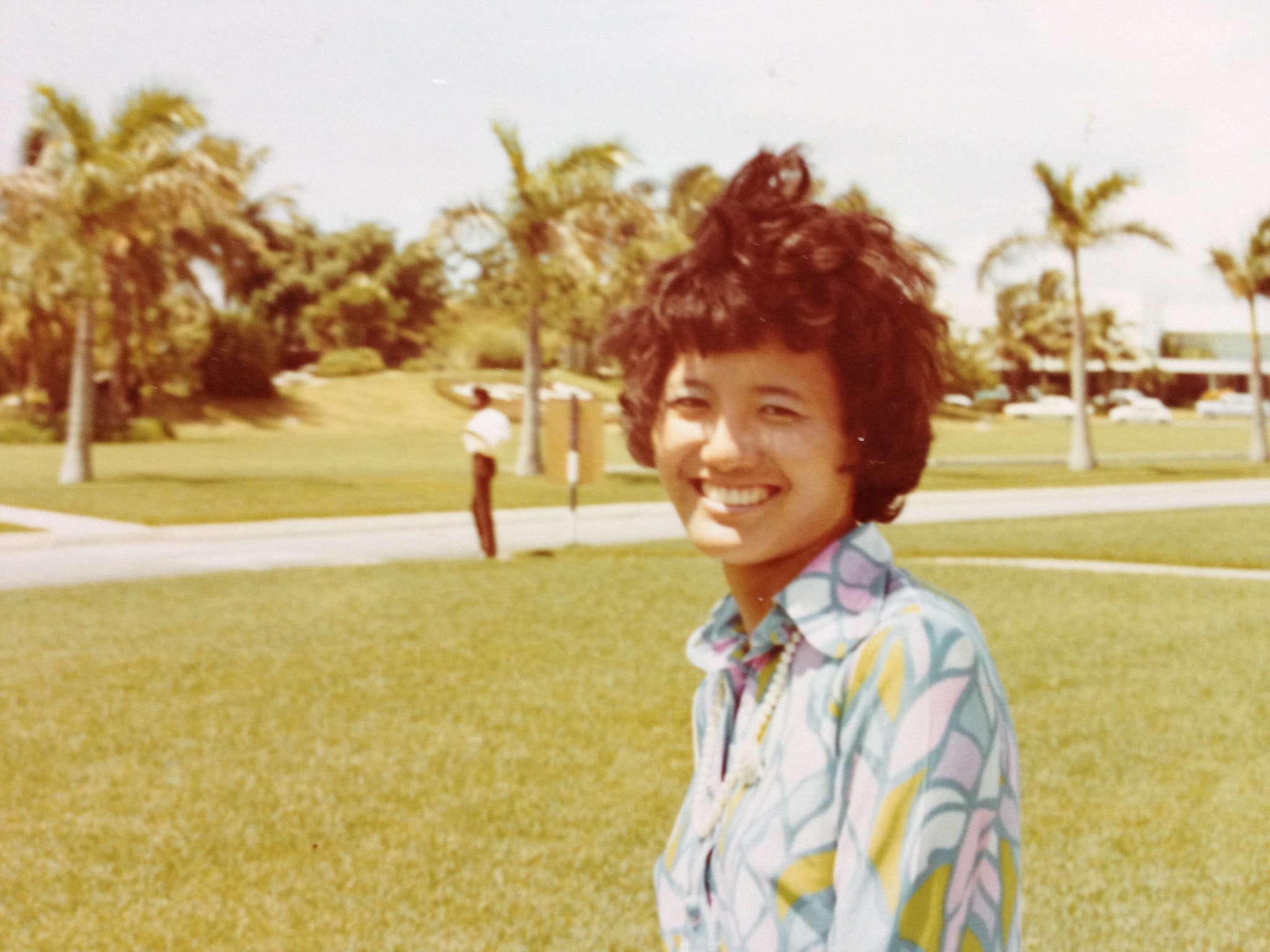 Headshot portrait of Denise Khor's mother outdoors in the Bahamas with palm trees in the background