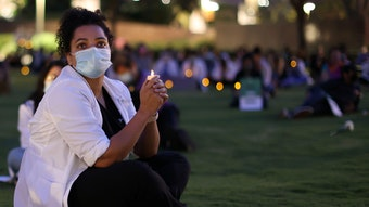 Student sitting on grass with candlelight, possibly at a vigil