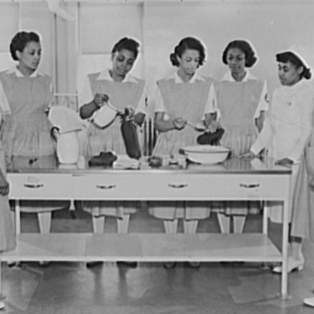 A black and white photo of six volunteer women nurse aides of color receiving training from a woman staff nurse of color.